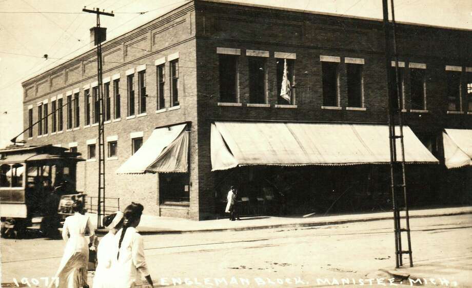 A trolley comes by the Engelmann Building located on the corner of River and Maple Street in the early 1920s.