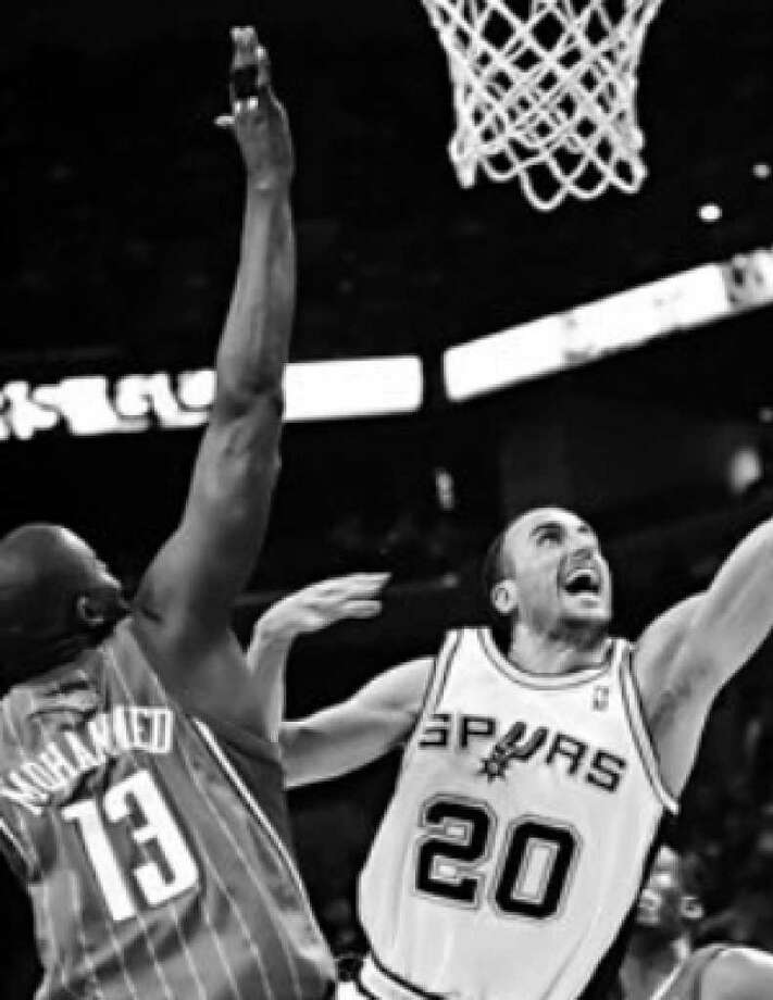 Manu Ginobili (20) slides between Charlotte's Nazr Mohammed (13) and Derrick Brown (4) for a basket during Friday's 104-85 Spurs win. He had 22 points, and 20 the game before.