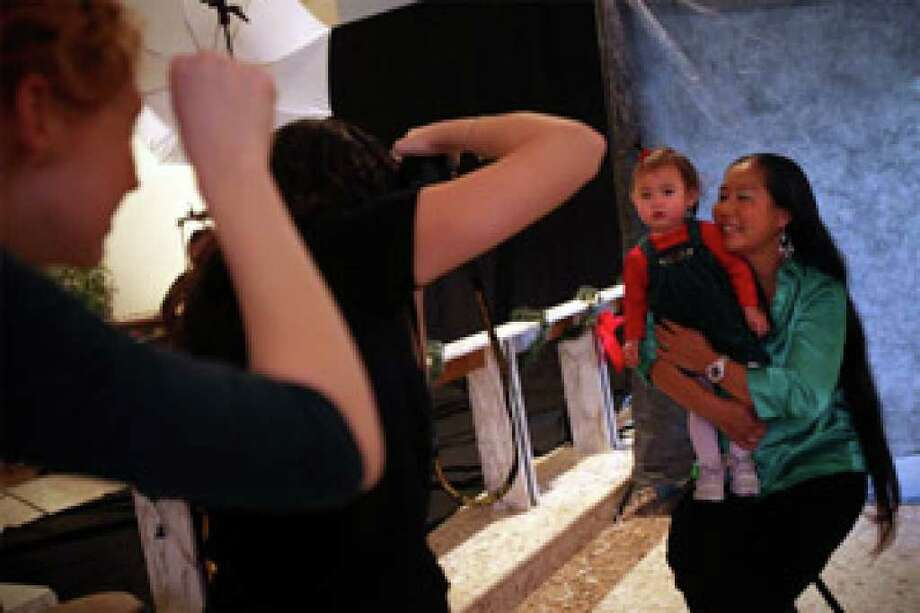 Photographer Samantha Davis makes a portrait of SAMMinistries shelter resident Joon Choo and her year-old daughter, Avaleena. Some 22 San Antonio photographers volunteered their equipment, expertise and time to take free portraits.