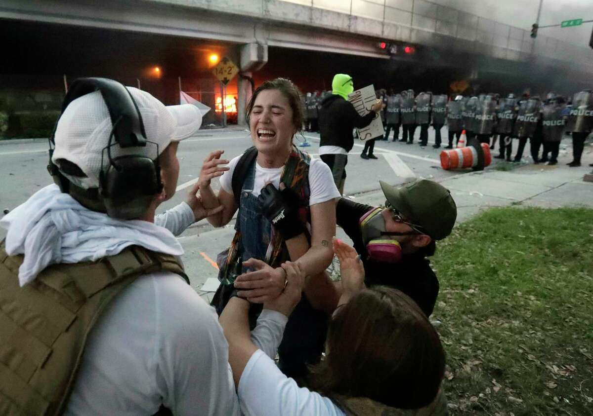 Protesters help a woman who was hit in the throat with a rubber bullet during a demonstration next to the city of Miami Police Department, Saturday, May 30, 2020, downtown in Miami. Protests were held throughout the country over the death of Floyd, a black man who was killed in police custody in Minneapolis on May 25.
