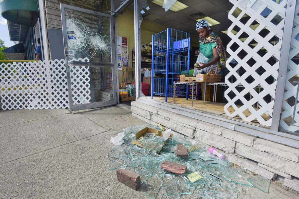 A woman shops just inside a broken window at Tay Market on Central Ave. on Sunday, May 31, 20202, in Albany, N.Y. People broke into the market late Saturday night the owner, Tay Ngo said. Ngo, who opened his business in 2012, showed up at 2:00 a.m. on Sunday to watch over his damaged store and to begin the cleaning process. (Paul Buckowski/Times Union)