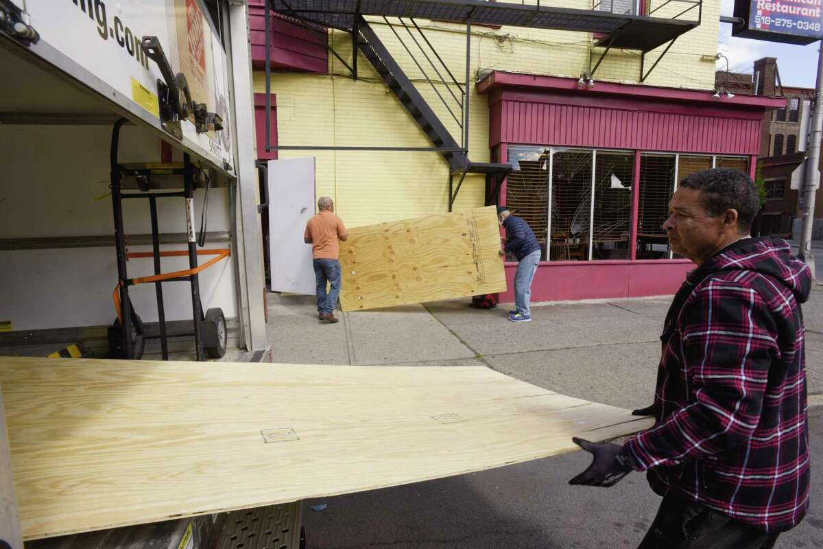 Sheets of plywood are pulled out of a truck to be installed over broken windows at Lo Nuestron Dominican Restaurant on Central Ave. on Sunday, May 31, 20202, in Albany, N.Y. People broke into the restaurant Saturday night and stole the cash register. (Paul Buckowski/Times Union)