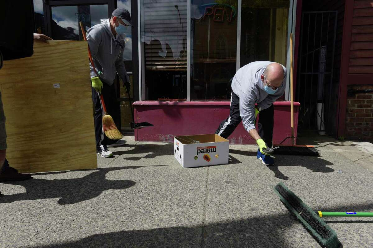 Pat Rowan, left, and Chris Cavanaugh, both from Malta, clean up glass and debris from the front of businesses on Central Ave. on Sunday, May 31, 20202, in Albany, N.Y. The two men came down to Albany to help clean up the area after people broke into businesses and looted stores Saturday night. (Paul Buckowski/Times Union)