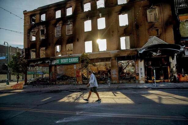 A man walks past a damaged building following overnight protests over the death of George Floyd, Sunday, May 31, 2020, in Minneapolis, Minn. Protests were held throughout the country over the death of Floyd, a black man who died after being restrained by Minneapolis police officers on May 25. (Elizabeth Flores/Star Tribune via AP)