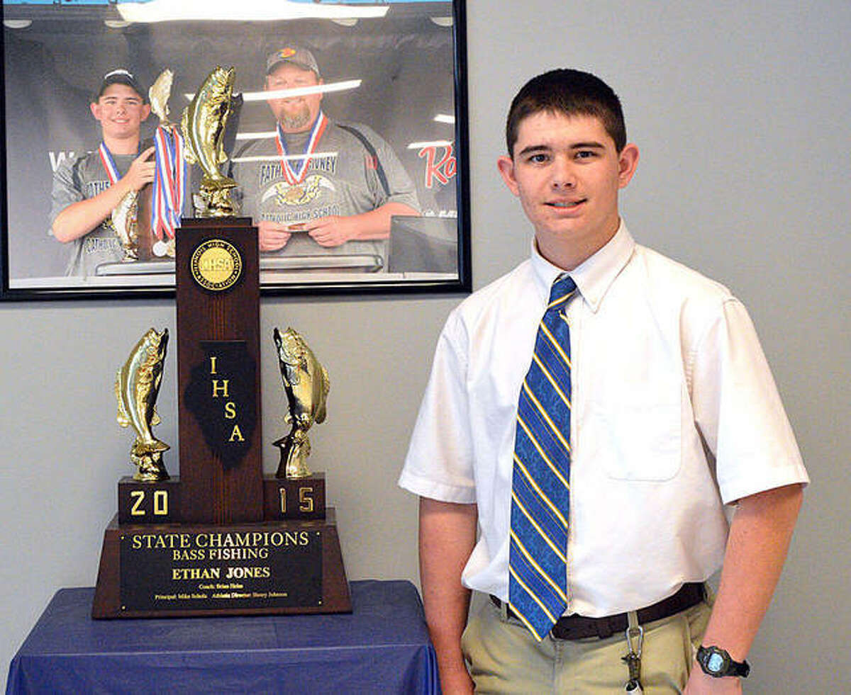 Father McGivney's Ethan Jones poses with the trophy he got for winning the IHSA state bass fishing tournament at Carlyle Lake.