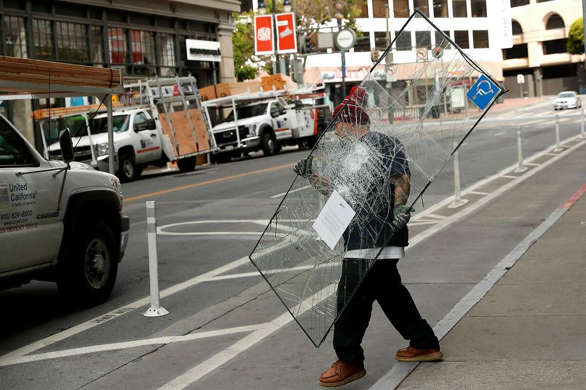 A United California Fire Protection employee carries a broken door window while boarding up Westfield Shopping Center in aftermath of looting in San Francisco, Calif., on Sunday, May 31, 2020.