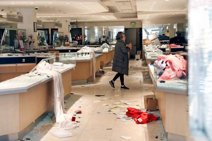 A woman walks through Grace Jewelry on O'Farrell Street in aftermath of looting in San Francisco, Calif., on Sunday, May 31, 2020.