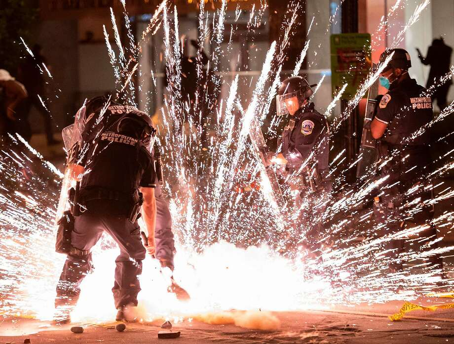 """A firecracker thrown by protesters explodes under police one block from the White House on May 30, 2020 in Washington DC, during a protest over the death of George Floyd, an unarmed black man, who died after a Minneapolis police officer kneeled on his neck for several minutes. Clashes broke out and major cities imposed curfews as America began another night of unrest Saturday with angry demonstrators ignoring warnings from President Donald Trump that his government would stop violent protests over police brutality """"cold."""" Photo: Andrew Caballero-Reynolds / AFP / Getty Images"""