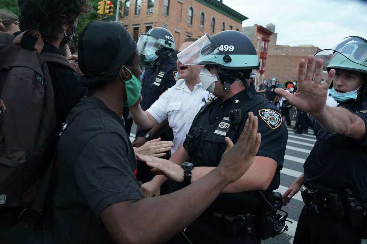 NYPD officers and protesters clash during a demonstration against the killing of George Floyd by Minneapolis police on Memorial Day, on May 30, 2020 in the Borough of Brooklyn in New York. - Demonstrations are being held across the US after George Floyd died in police custody on May 25. (Photo by Bryan R. Smith / AFP)