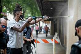 San Antonio Spurs guard Lonnie Walker, center, helps to clean off graffiti in downtown San Antonio, Texas, U.S. on Sunday, May 31, 2020 following a night of violent protests. The day followed a night of protests in downtown San Antonio where business front?•s were damaged and some businesses were looted. Saturday saw hundreds of people gather in downtown San Antonio to protest the death of George Floyd in Minnesota while he was in police custody.