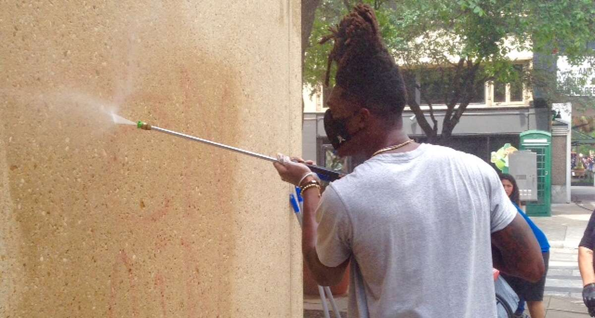 The Spurs' Lonnie Walker helps remove graffiti from a building Sunday morning in downtown San Antonio following Saturday night's peaceful protest march in memory of George Floyd, the African American who died last week in police custody in Minneapolis. After the march in San Antonio, there was a violent clash between police and rioters that left storefronts and buildings damaged.