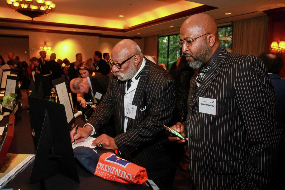Manson Johnson, left, and Timothy McNeil look at auction items at the American Leadership Forum Houston/Gulf Coast Chapter Joseph Jaworski Leadership Award Dinner. (For the Chronicle/Gary Fountain, April 26, 2018)