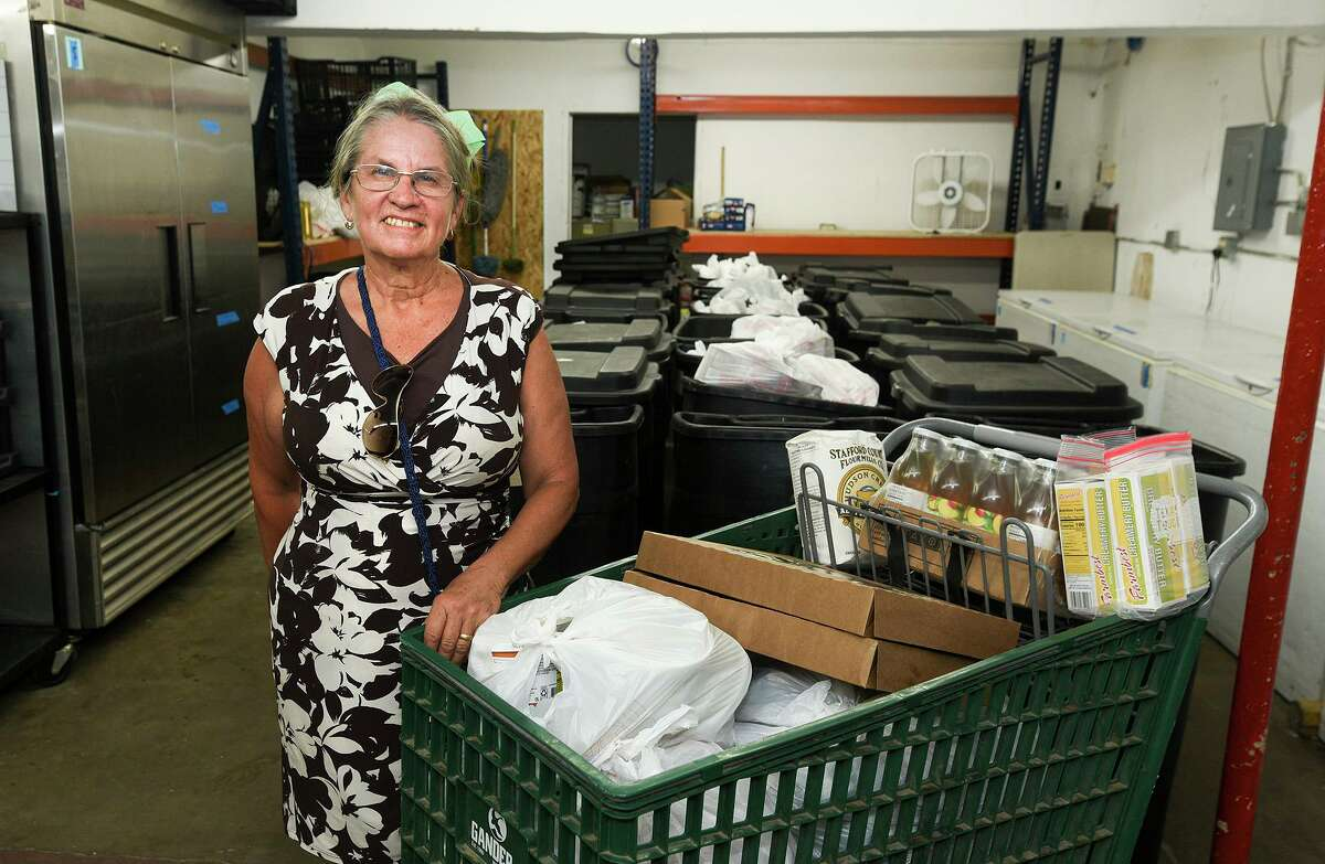 Volunteers Serving the Need's Gigi Ramos is pictured Friday inside the thrift store next to a shopping cart filled with groceries. The organization will provide 100 veterans in need with a full cart each.