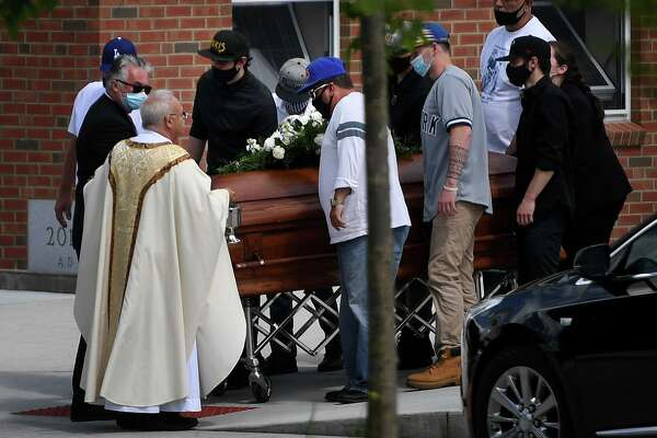 Pallbearers bring the casket of Nicholas Eisele to a waiting hearse following funeral services outside Rose of Lima Church in Newtown, Conn. on Sunday, May 31, 2020.