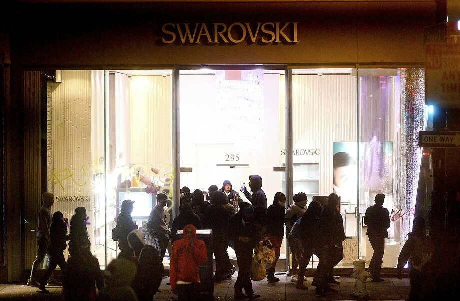 People vandalize a Swarovski store in San Francisco's Union Square on Saturday, May 30, 2020. Widespread vandalizing occurred at stores throughout San Francisco following the death of George Floyd, a handcuffed black man in police custody in Minneapolis. (AP Photo/Noah Berger) Photo: Noah Berger, Associated Press