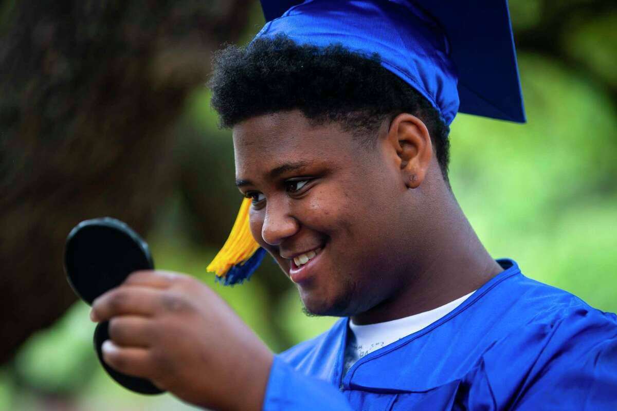 Correy Lettsome, 18, smiles as he checks his graduation cap during a celebration organized by Child Protective Services on Sunday, May 31, 2020. Lettsome, a graduate from Klein High School, hopes to become a chef. He joined other seniors in their caps and gowns for a personal photo shoot to commemorate their achievement.