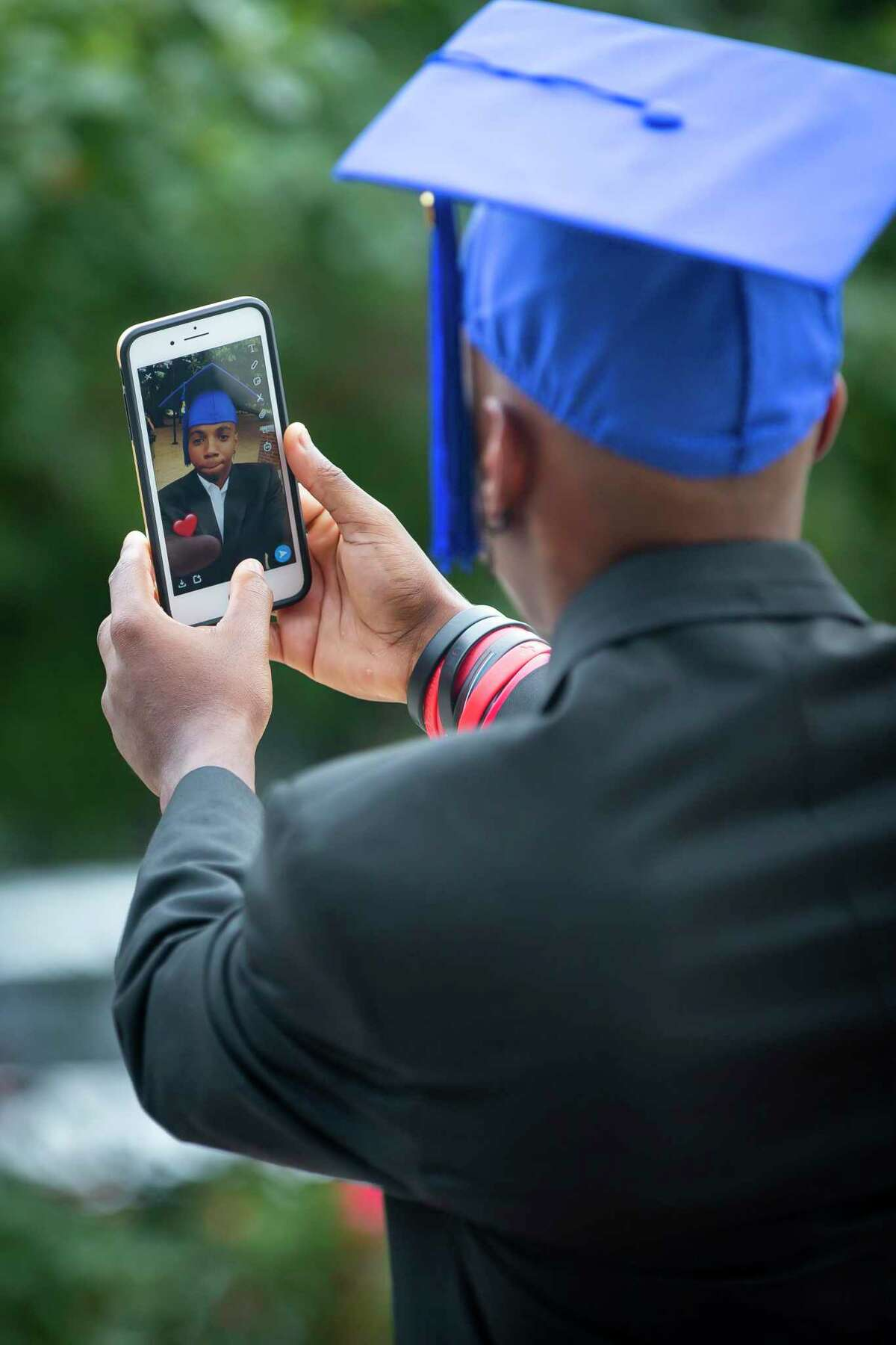 Oronde Sinclair poses for a selfie in a graduation cap during a graduation celebration organized by Child Protective Services on Sunday, May 31, 2020. Seniors donned their caps and gowns for a personal photo shoot to commemorate their achievement.
