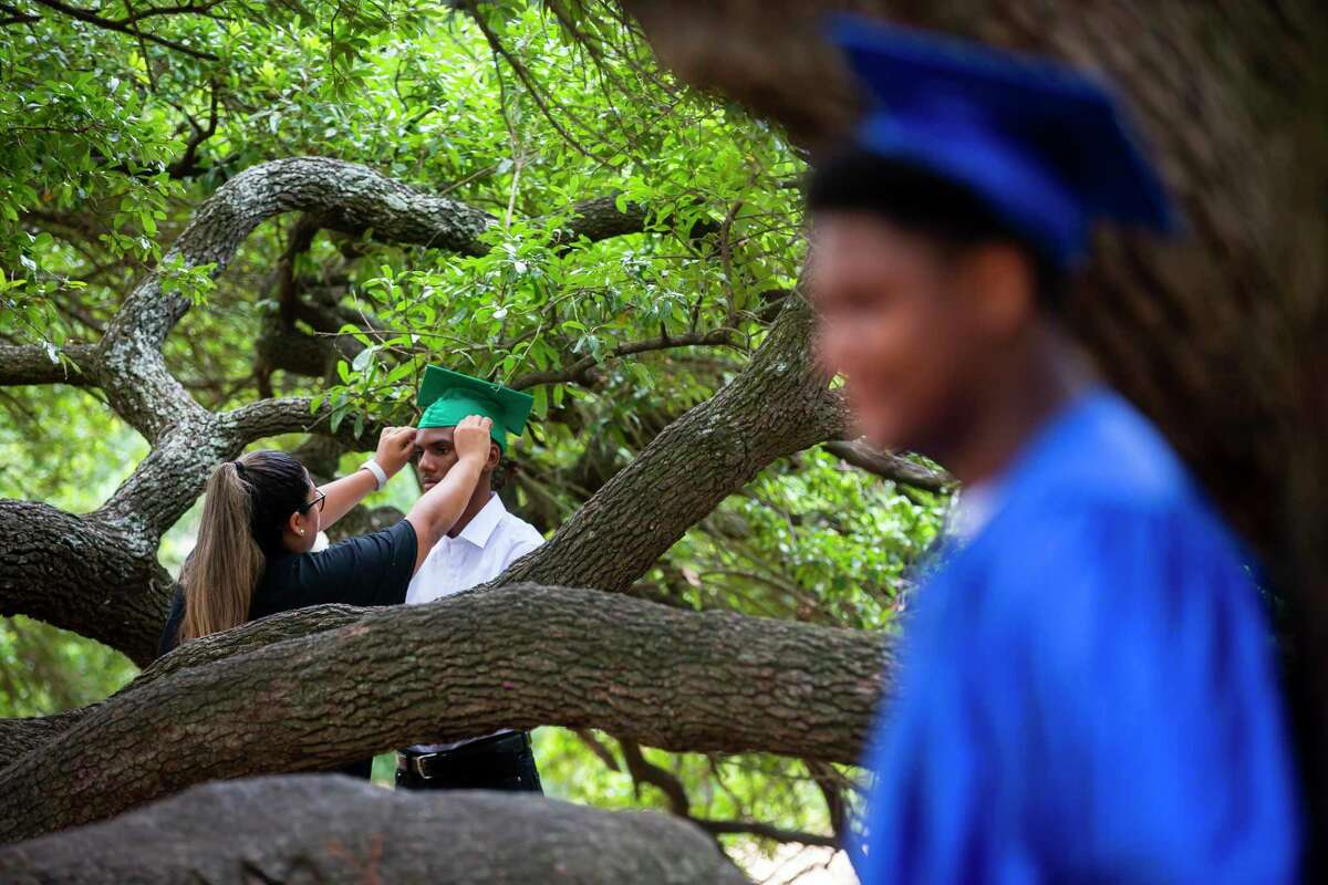 CPS employee and photographer Ashley Bermudez adjusts the cap of Shemar Williams, 17, during a graduation celebration organized by Child Protective Services on Sunday, May 31, 2020. Seniors donned their caps and gowns for a personal photo shoot to commemorate their achievement.
