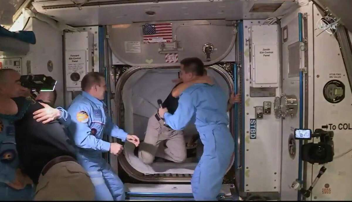 This NASA video frame grab image shows SpaceXs Crew Dragon NASA astronauts Douglas Hurley (right) and Robert Behnken (left) arriving after the hatch opened to the International Space Station on May 31, 2020 with other astronauts. (Photo by HANDOUT/NASA TV/AFP via Getty Images)