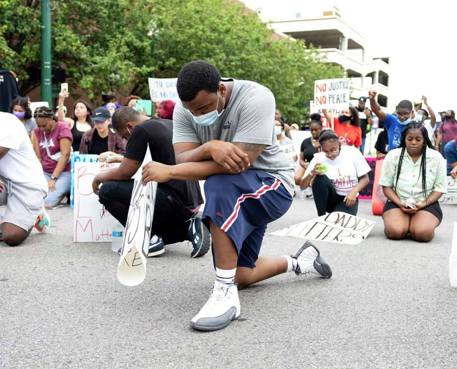 A demonstrator kneels for a moment of silence in honor of George Floyd in downtown Conroe, Sunday, May 31, 2020. Approximately over 100 people participate in the demonstration. Photo: Gustavo Huerta, Houston Chronicle / Staff Photographer / Houston Chronicle © 2020