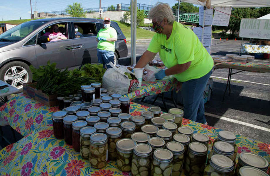 Becky Sancamper, foreground, bags an order for a drive-up customer at the Alton Farmers' Market Saturday at 501 Landmarks Blvd. in Alton. The market will return to walk-through shopping Saturday, June 6. Photo: Jeanie Stephens |The Telegraph