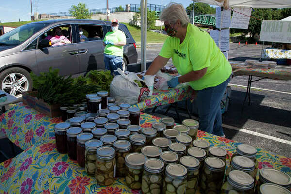 Becky Sancamper, foreground, bags an order for a drive-up customer at the Alton Farmers' Market Saturday at 501 Landmarks Blvd. in Alton. The market will return to walk-through shopping Saturday, June 6.