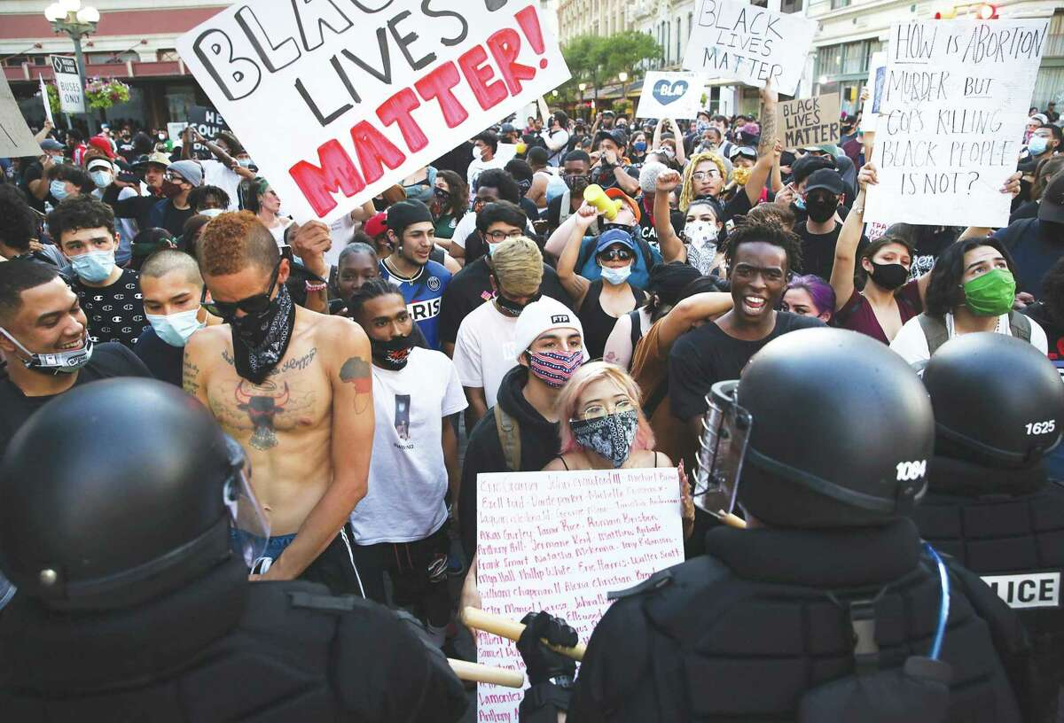 Police and protesters upset about the death of Texan George Floyd face off in Alamo Plaza near the Alamo on Saturday.