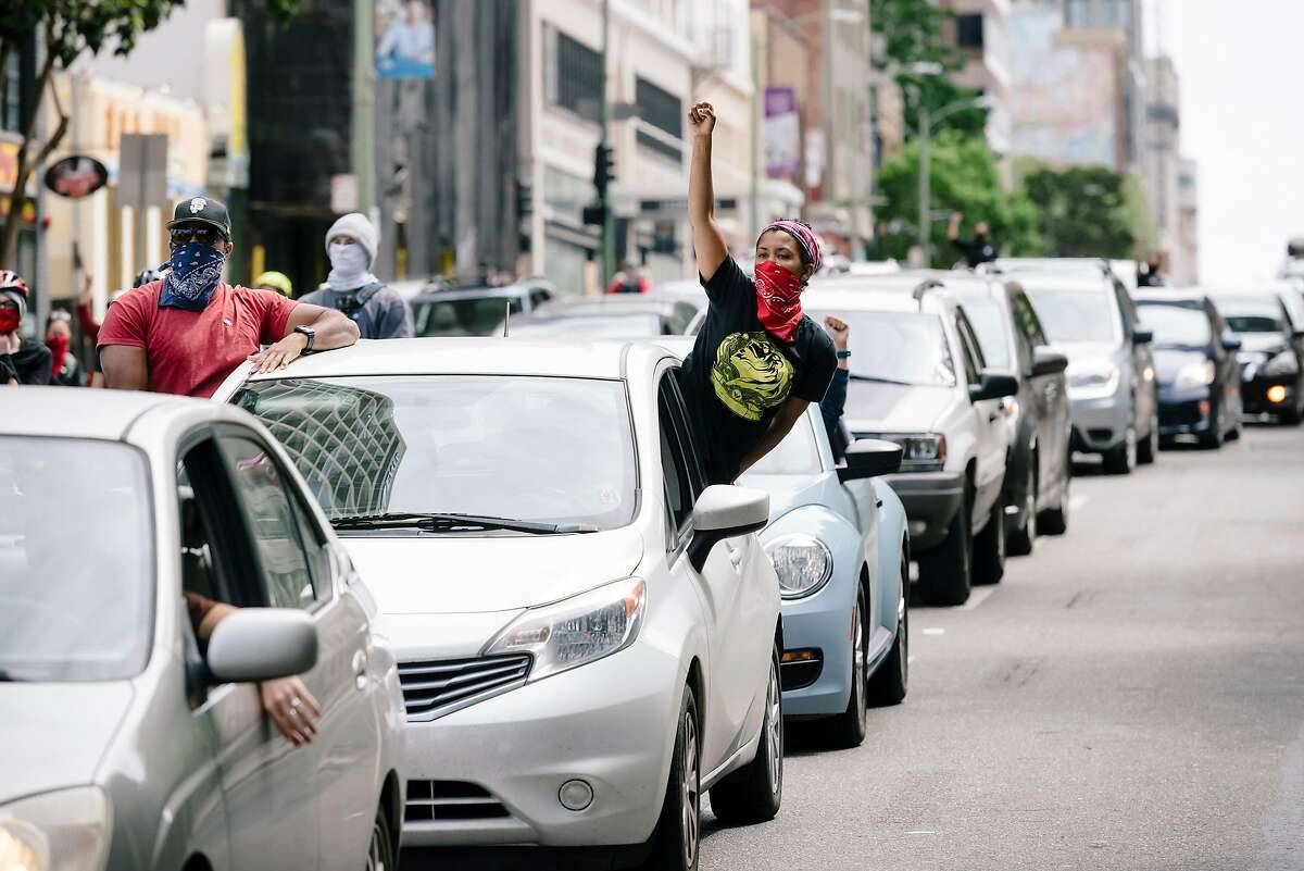 People raised their fists from their cars during a Justice for George Floyd & Breonna Taylor Car Caravan in Oakland, Calif, on Sunday, May 31, 2020.