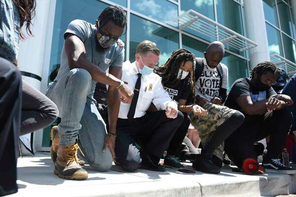 Stamford Police Chief Tim Shaw, second from left, takes a knee with #JusticeForBrunch Black Lives Matter protest organizers outside the Stamford Police Department in Stamford on Sunday. About 500 people marched from Harbor Point to the Stamford Police Station in honor of George Floyd and all other victims of police brutality.
