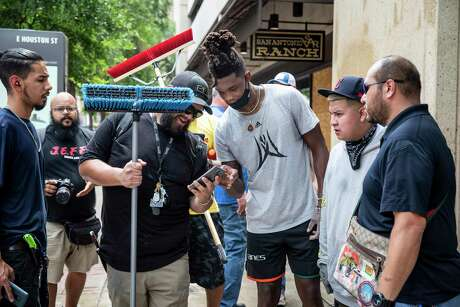 Spurs guard Lonnie Walker, center right, takes a selfie with another volunteer as they clean off graffiti in downtown San Antonio on May 31, 2020, following a night of violent protests. The day followed a night of protests in downtown San Antonio where business fronts were damaged and some businesses were looted. Saturday saw hundreds of people gather in downtown San Antonio to protest the death of George Floyd in Minnesota while he was in police custody.