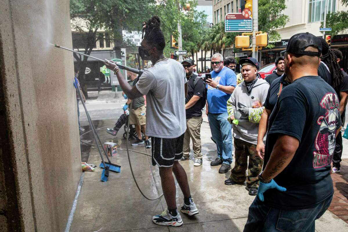 Spurs guard Lonnie Walker, left, helps to clean off graffiti in downtown San Antonio on May 31, 2020, following a night of violent protests. The day followed a night of protests in downtown San Antonio where business fronts were damaged and some businesses were looted. Saturday saw hundreds of people gather in downtown San Antonio to protest the death of George Floyd in Minnesota while he was in police custody.