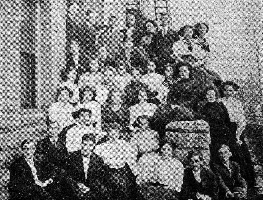 Members of the high school Class of 1910 pose for a photo outside the former high school that was once located on the corner of Oak and First streets.