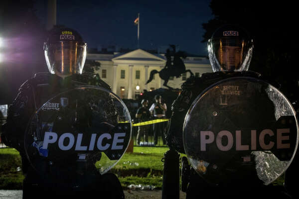 Members of the U.S. Secret Service stand guard in front of the White House as demonstrators gather nearby on Saturday to protest the death of George Floyd.