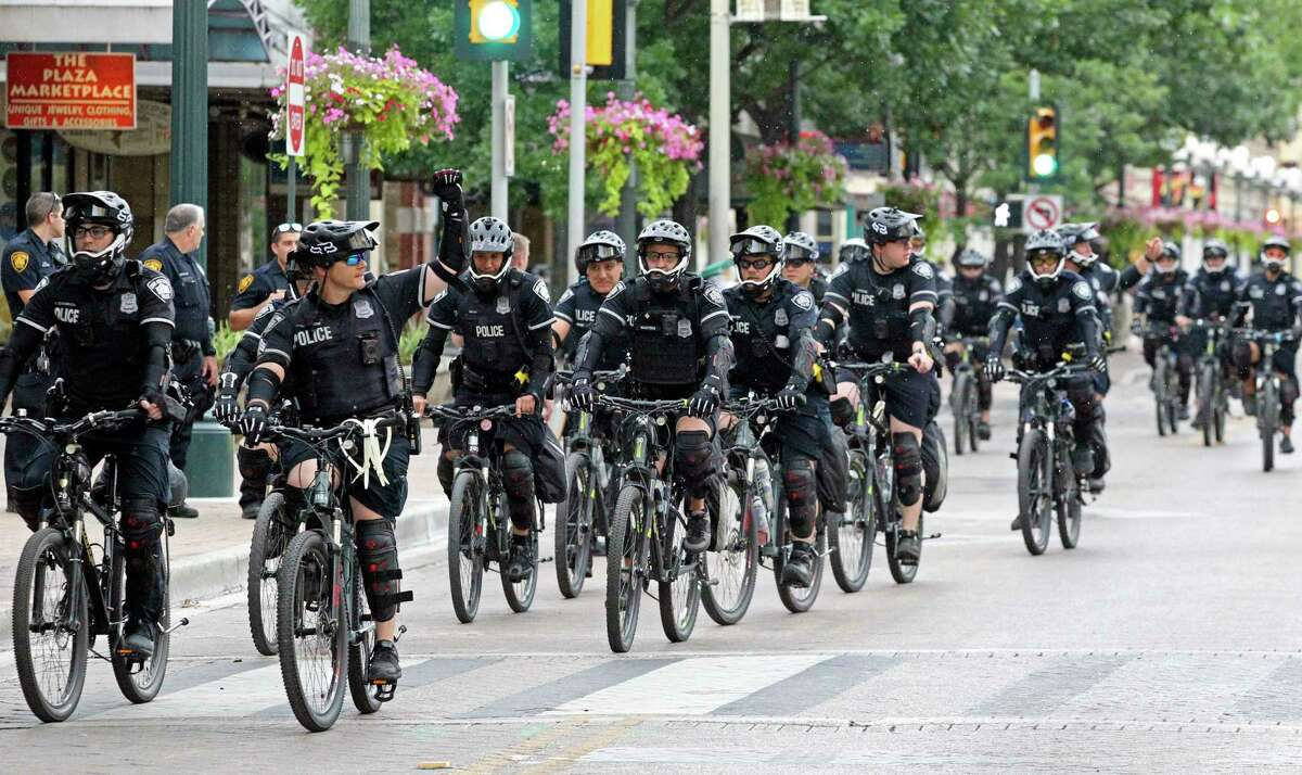 Cops on bikes ride through Alamo Plaza on the day after the downtown riots on May 31, 2020.