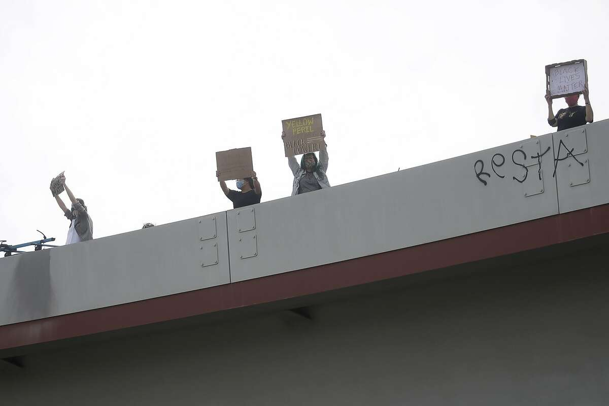 People hold up signs on an offramp over Interstate 80 in Oakland, Calif., Sunday, May 31, 2020, at a protest over the Memorial Day death of George Floyd. Floyd was a black man who was killed in police custody in Minneapolis on May 25. (AP Photo/Jeff Chiu)