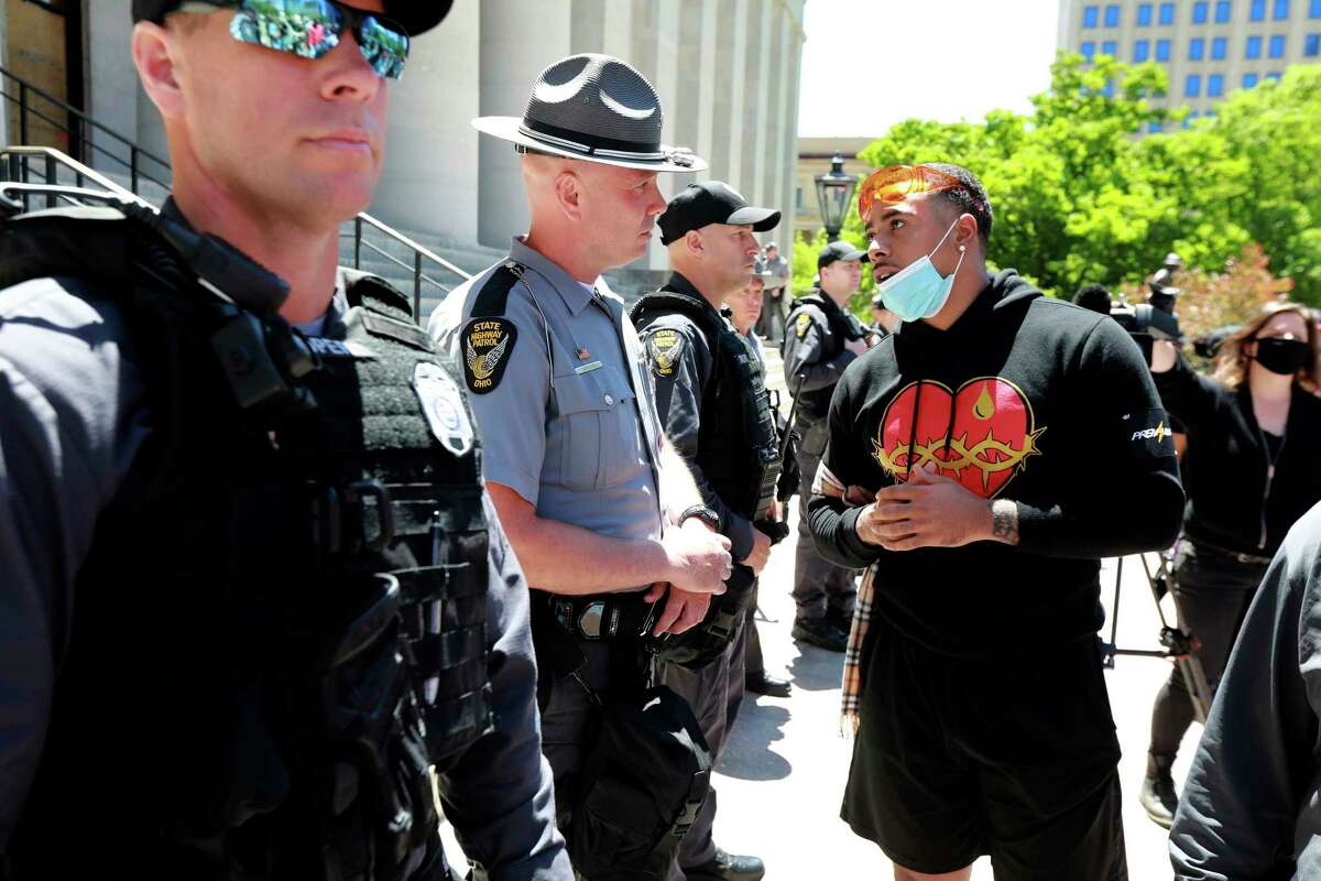 Jalon Lewis talks with Ohio State Trooper Weaver (no first name given) at the Ohio Statehouse in Columbus during a peaceful Sunday, May 31, 2020 protest over the death of George Floyd in Minnesota. Lewis, 23, related a story about being profiled and having his car searched as he drove home from his college graduation ceremony at Livingstone College, an historically black college. Lewis said trooper Weaver listened and understood. (Doral Chenoweth/The Columbus Dispatch via AP)