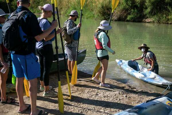 "Liam Duggan helps river tour participants into the kayaks while wearing a mask in the Rio Grande River at the Big Band Ranch State Park in Texas, on May 26, 2020. According to Duggan, very few of the river guides in Terlingua are working due the pandemic, ""it's been strange"" says Duggan. The Far Flung Outdoor Center has implemented several ways of keeping guests and guides safe including minimal physical contact, driving separately to the put-in spot and guides wearing masks while helping participants. ""Short term we're worried about people's safety but long term it's our (guides) safety we're concerned about,"" says Duggan."