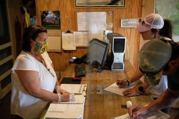 Debra Guerrero wears a mask behind plexiglass while helping visitors Shantel and Brian Cloud fill out paperwork in her Big Bend Stables office in Terlingua, Texas, on May 26, 2020.