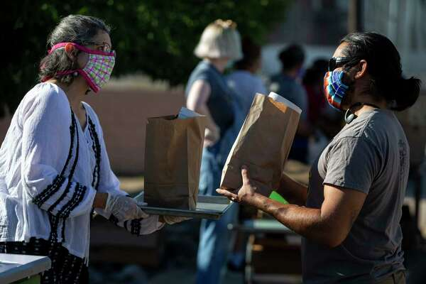Annette Mendoza offers bags of art supplies from the Marfa Studio of Arts to a man picking up lunches outside the Carl P. Robinson Cafeteria in Marfa.
