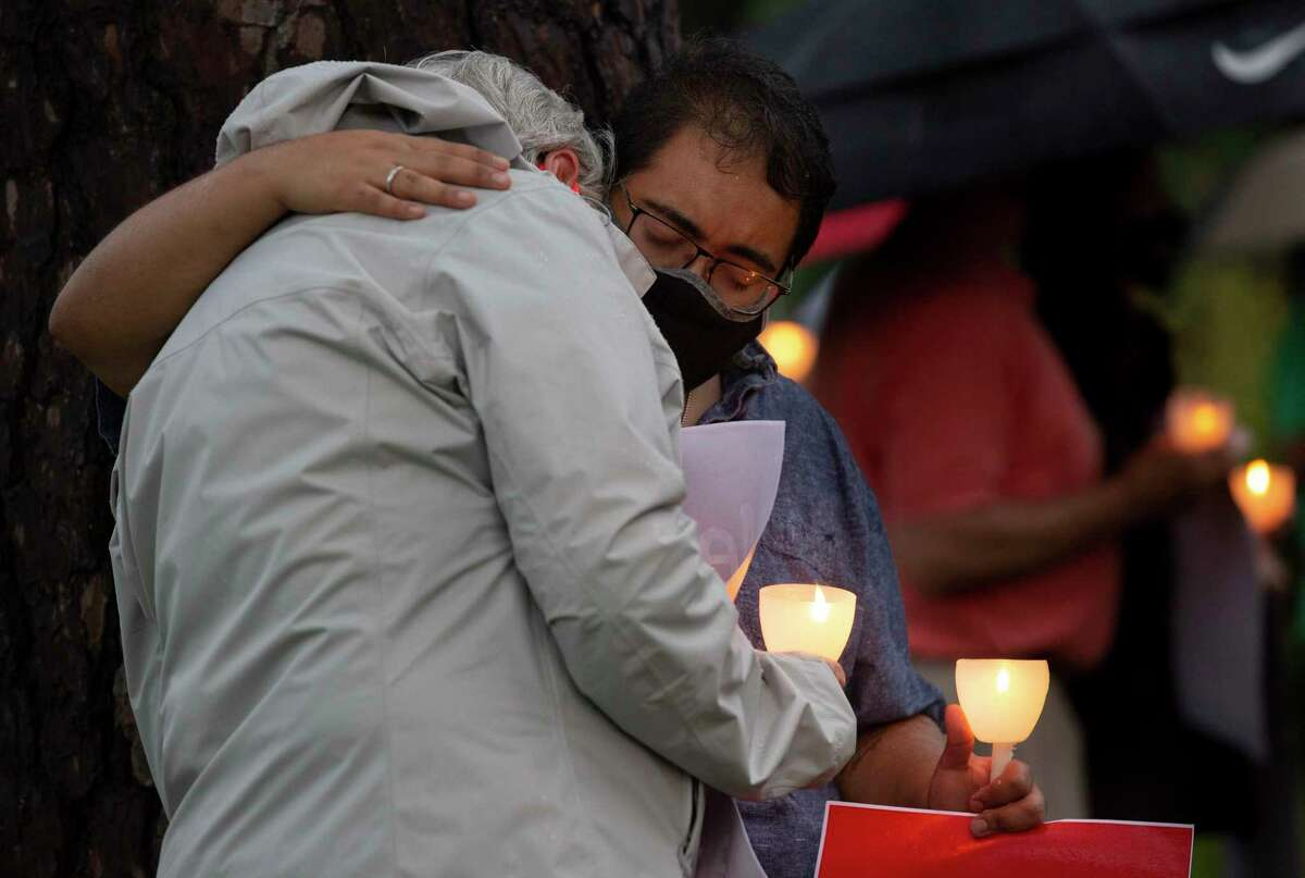 Kiersten Andrews, front, and Alex Martinez embrace each other during the moment of silence at a vigil for George Floyd, who died in Minneapolis Police Department custody earlier this week, Sunday, May 31, 2020, at Metropolitan Community Church in Houston. The vigil held an eight-minute-and-46-seconds moment of silence, the time that white MPD officer, Derek Chauvin, kept his knee on Floyd's neck, to remember Floyd.