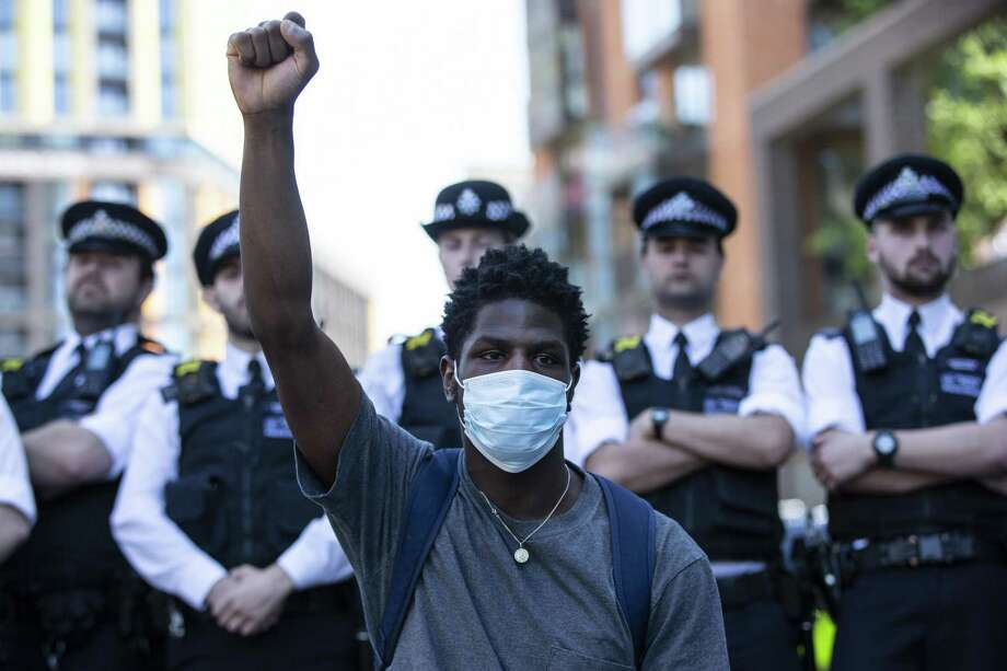 """LONDON, ENGLAND - MAY 31: Police officers block a road close to the Embassy of the United States of America as people join in a spontaneous Black Lives Matter march through central London to protest the death of George Floyd in Minneapolis and in support of the demonstrations in North America on May 31, 2020 in London, England. The death of an African-American man, George Floyd, at the hands of police in Minneapolis has sparked violent protests across the USA. A video of the incident, taken by a bystander and posted on social media, showed Floyd's neck being pinned to the ground by police officer, Derek Chauvin, as he repeatedly said """"I cant breathe"""". Chauvin was fired along with three other officers and has been charged with third-degree murder and manslaughter. (Photo by Hollie Adams/Getty Images) Photo: Hollie Adams, Stringer / Getty Images / 2020 Getty Images"""