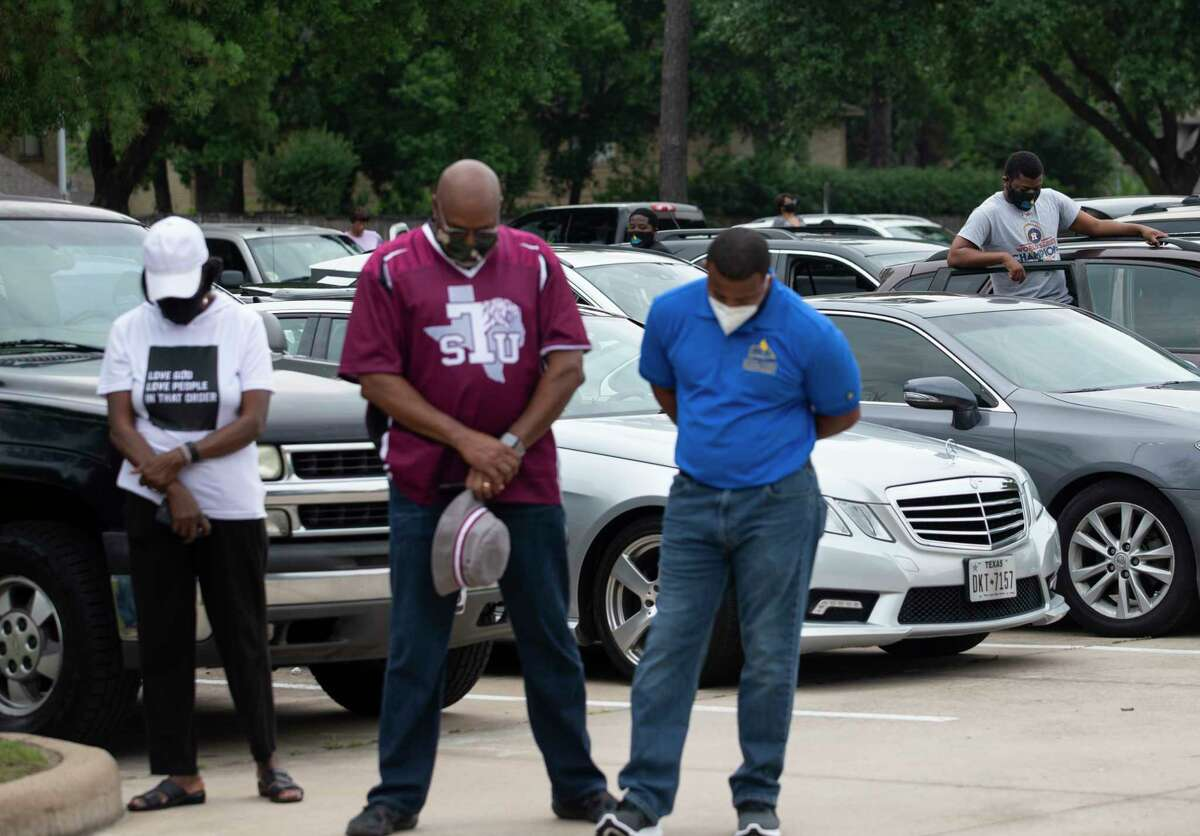 """People join U.S. Rep. Sheila Jackson Lee, Pastor and Dr. Paul Cannings, Mayor Sylvester Turner, Houston Police Chief Art Acevedo and Houston Fire Chief Sam Peña for a prayer for the city and for George Floyd's family the """"Pull Up & Praise"""" drive-thru fellowship service Sunday, May 31, 2020, at The Christian Outreach Center in Houston. Floyd died in custody of the Minneapolis Police Department earlier this week."""