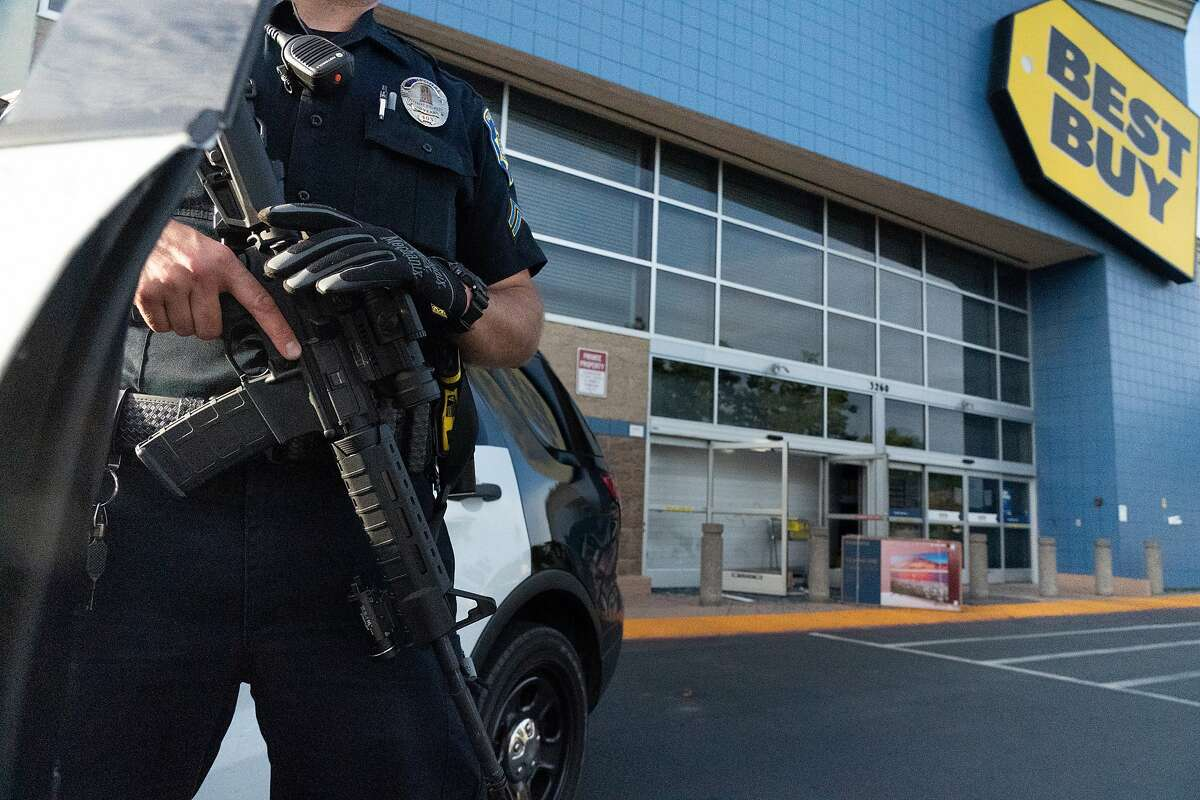 Police guard a Best Buy after it was looted on Sunday, May 31, 2020 in Walnut Creek, Calif.
