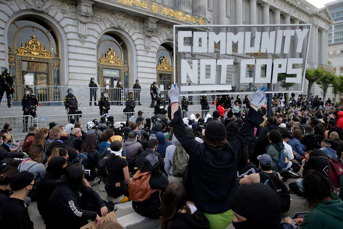 A protester holds a sign up as thousands of protesters gathered at City Hall took a knee and chanted for the police to do so as well in San Francisco, Calif., on Sunday, May 31, 2020. It was the third straight night of worldwide solidarity protests over the killing of George Floyd in Minneapolis by police earlier in the week.