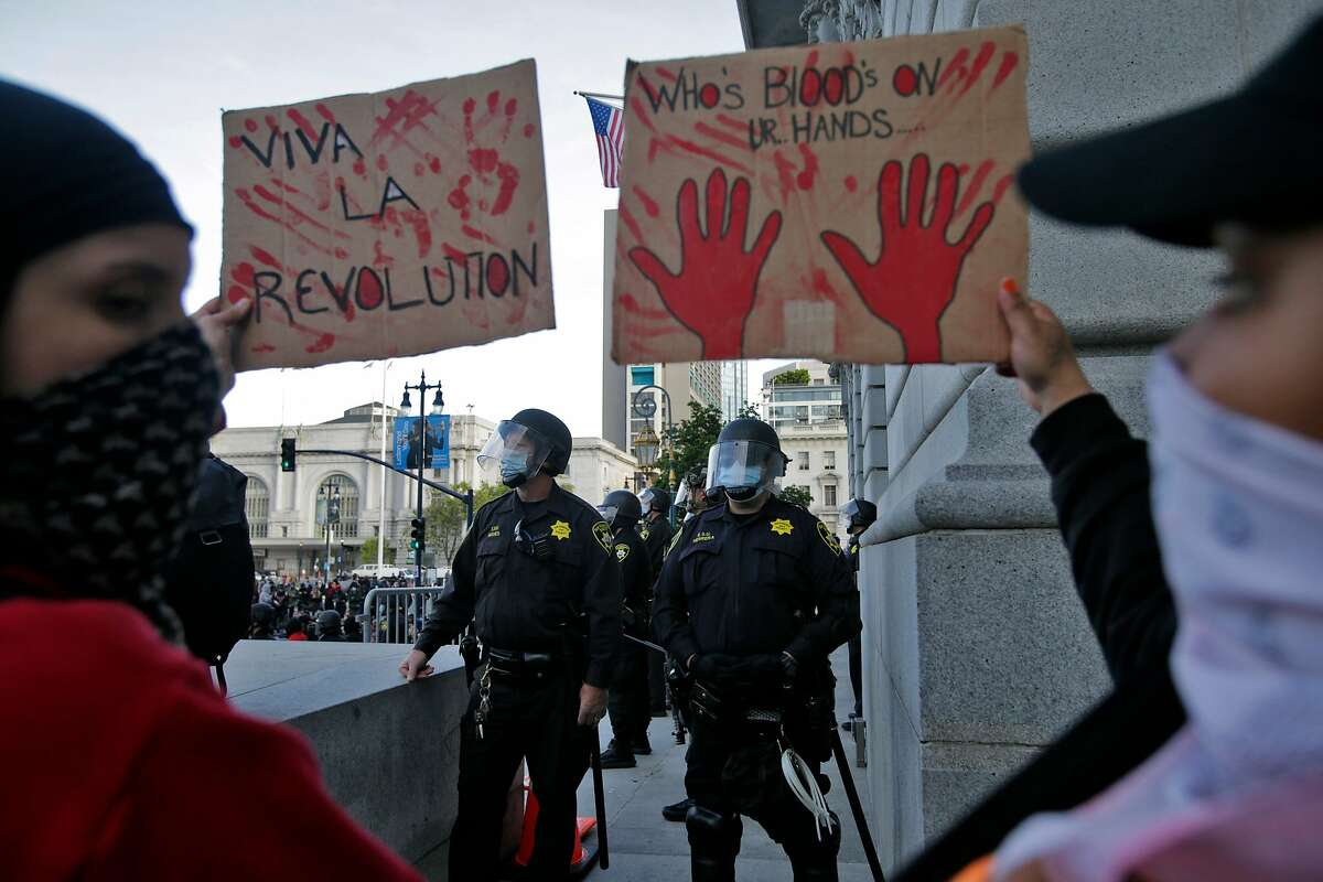 Melvin Keihr, right, and Kalani Estis hold signs near a line of police guarding against protesters gathered at City Hall in San Francisco, Calif., on Sunday, May 31, 2020. It was the third straight night of worldwide solidarity protests over the killing of George Floyd in Minneapolis by police earlier in the week.