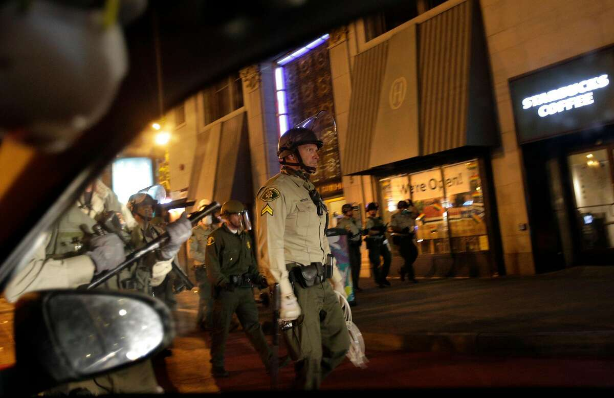 A line of Santa Barbara Sheriff's officers walk along 3rd Street from Market Street as curfew takes hold in San Francisco on Sunday, May 31, 2020. Mayor London Breed issued a curfew following several nights of violent protests and looting in the city.