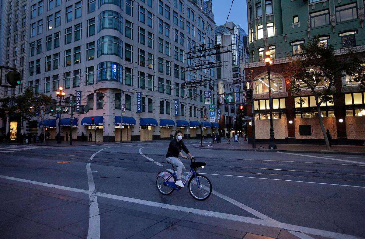A bicyclist rides along an empty Market Street toward as police officers from multiple agencies keep an eye on downtown when curfew takes hold in San Francisco, Calif., on Sunday, May 31, 2020. Mayor London Breed issued a curfew following several nights of violent protests and looting in the city.