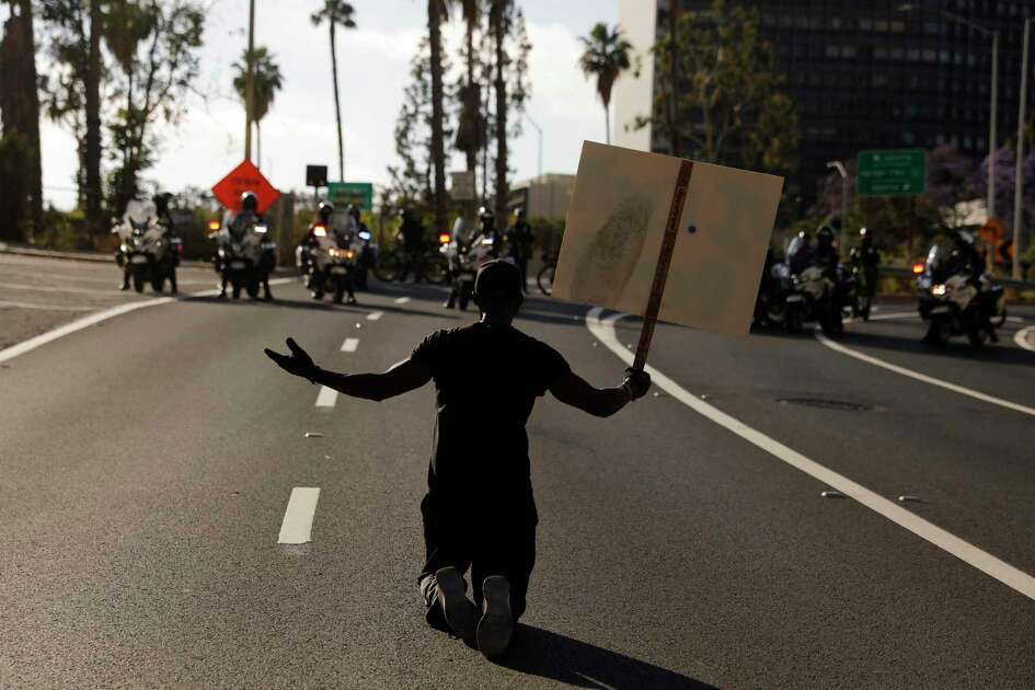 """A man kneels on the street in front of police officers while chanting """"I can't breathe"""" during a protest over the death of George Floyd, Friday, May 29, 2020, in Los Angeles. Floyd died Memorial Day while in police custody in Minneapolis. (AP Photo/Jae C. Hong)"""