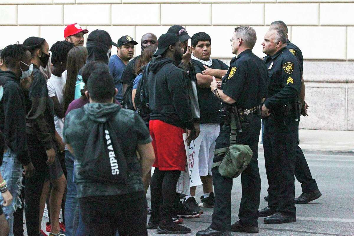Police come forward to discuss matters with demonstrators gathered next to the federal building on Alamo Plaza on the day after the downtown riots on May 31, 2020.