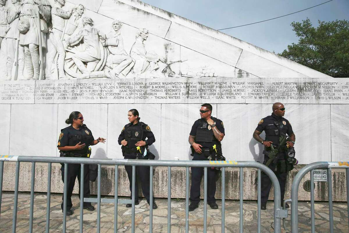Police officers guard the cenotaph in Alamo Plaza on the day after the downtown riots on May 31, 2020.